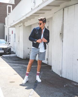 Cómo combinar: chaqueta vaquera azul marino, camisa de vestir celeste, pantalones cortos grises, tenis de cuero blancos