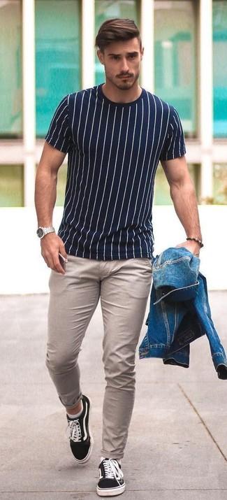 Cómo combinar: chaqueta vaquera azul, camiseta con cuello circular de rayas verticales en blanco y azul marino, pantalón chino en beige, tenis de lona negros