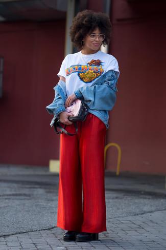 Cómo combinar: chaqueta vaquera celeste, camiseta con cuello circular estampada blanca, pantalones anchos rojos, botines con cuña de cuero negros