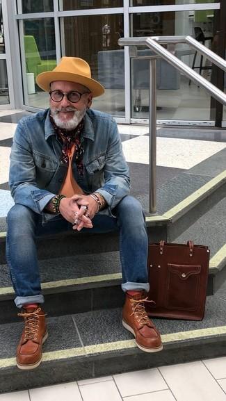 Cómo combinar: chaqueta vaquera azul, camiseta con cuello circular naranja, vaqueros pitillo azules, botas de trabajo de cuero marrónes