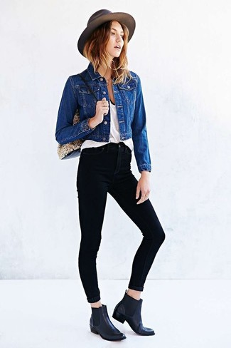 Cómo combinar: chaqueta vaquera azul, camiseta sin manga blanca, vaqueros pitillo negros, botines chelsea de cuero negros