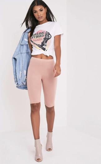 Cómo combinar: chaqueta vaquera desgastada celeste, camiseta con cuello circular estampada en blanco y rosa, mallas ciclistas rosadas, botines de cuero con recorte en beige