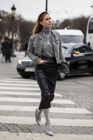 Cómo combinar: chaqueta vaquera gris, jersey con cuello circular gris, falda midi de cuero negra, zapatos de tacón de lona grises