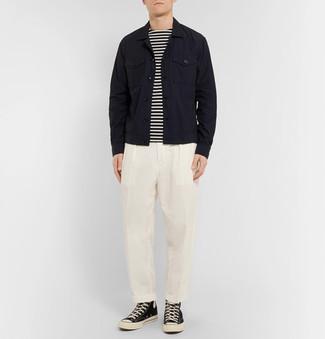 Cómo combinar: chaqueta vaquera negra, camiseta de manga larga de rayas horizontales en blanco y negro, pantalón de vestir blanco, zapatillas altas de lona en negro y blanco