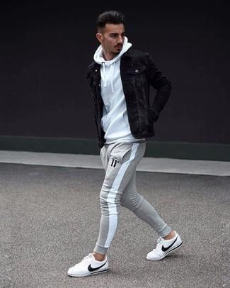 Cómo combinar: chaqueta vaquera negra, sudadera con capucha blanca, pantalón de chándal gris, tenis de cuero blancos
