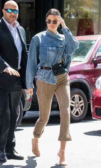 Cómo combinar: chaqueta vaquera azul, pantalones pitillo de tartán marrónes, sandalias de tacón de goma transparentes, riñonera de cuero negra