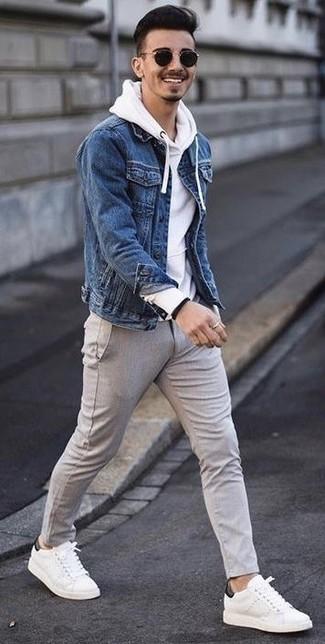 Cómo combinar: chaqueta vaquera azul, sudadera con capucha blanca, pantalón chino de lana gris, tenis de cuero blancos