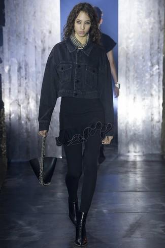 Cómo combinar: chaqueta vaquera negra, vestido ajustado con volante negro, botines de cuero negros, cartera de cuero negra