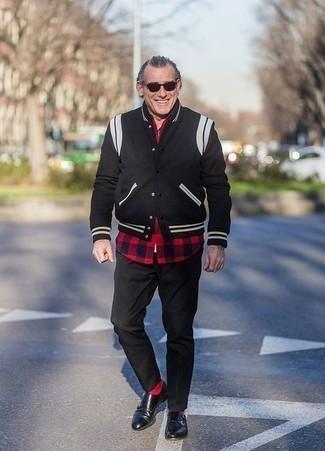 Look de moda: Chaqueta varsity negra, Camisa de manga larga de cuadro vichy en rojo y negro, Pantalón chino negro, Zapatos con doble hebilla de cuero negros