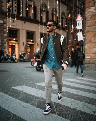 Cómo combinar: chaqueta varsity en negro y blanco, camisa vaquera azul, pantalón chino de lana gris, tenis de lona en negro y blanco