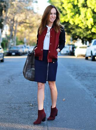 Cómo combinar: chaqueta varsity burdeos, camiseta con cuello circular estampada en blanco y negro, falda lápiz azul marino, botines de ante burdeos