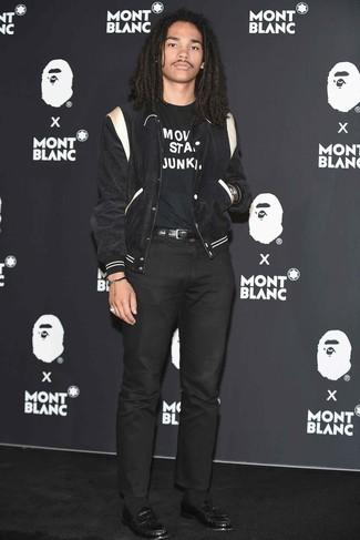 Cómo combinar: chaqueta varsity en negro y blanco, camiseta con cuello circular estampada en negro y blanco, pantalón chino negro, mocasín de cuero negro