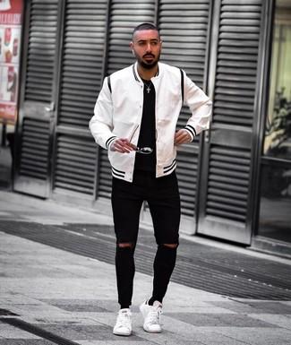 Cómo combinar: chaqueta varsity en blanco y negro, camiseta con cuello circular negra, vaqueros pitillo desgastados negros, tenis de cuero blancos