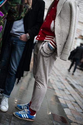 Empareja una chaqueta varsity con un pantalón chino gris para un almuerzo en domingo con amigos. Un par de tenis azules se integra perfectamente con diversos looks.