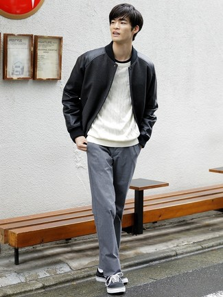Intenta ponerse una chaqueta varsity y un pantalón chino gris para lidiar sin esfuerzo con lo que sea que te traiga el día. Tenis de lona en negro y blanco son una opción grandiosa para completar este atuendo.