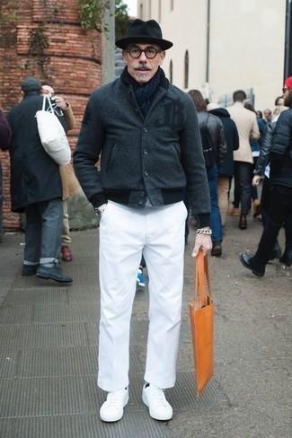 Cómo combinar una bolsa tote de cuero naranja: Utiliza una chaqueta varsity en gris oscuro y una bolsa tote de cuero naranja para un look agradable de fin de semana. Tenis de cuero blancos proporcionarán una estética clásica al conjunto.