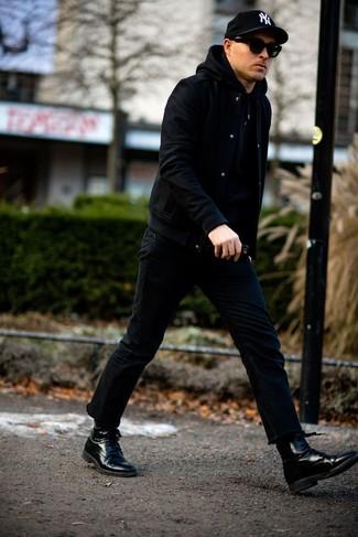 Cómo combinar una chaqueta varsity negra: Ponte una chaqueta varsity negra y unos vaqueros negros para cualquier sorpresa que haya en el día. Dale onda a tu ropa con botas formales de cuero negras.