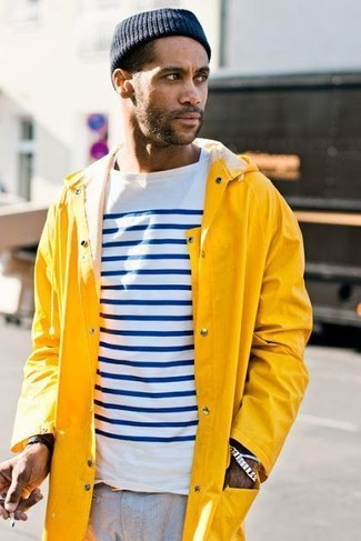 Cómo combinar: chubasquero amarillo, camiseta de manga larga de rayas horizontales en blanco y azul marino, pantalón chino gris, gorro azul marino