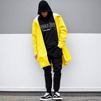 Cómo combinar: chubasquero amarillo, sudadera con capucha estampada en negro y blanco, pantalón de chándal negro, tenis de ante negros