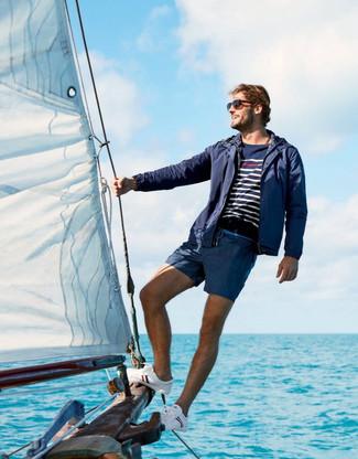 Cómo combinar: chubasquero azul marino, jersey con cuello circular de rayas horizontales en azul marino y blanco, shorts de baño azul marino, tenis de lona blancos