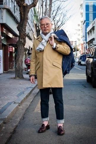 Un mocasín con borlas de vestir con unos vaqueros azul marino: Equípate un chubasquero marrón claro junto a unos vaqueros azul marino para una vestimenta cómoda que queda muy bien junta. Con el calzado, sé más clásico y elige un par de mocasín con borlas.