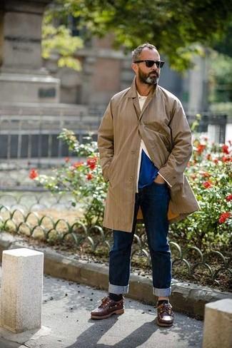 Cómo combinar: chubasquero marrón claro, camisa de manga larga en beige, camiseta con cuello circular azul, vaqueros azul marino