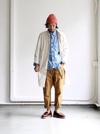Cómo combinar: chubasquero en beige, camisa vaquera celeste, camiseta con cuello circular blanca, pantalón chino marrón claro