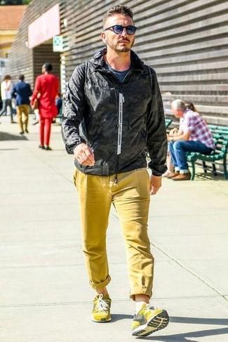 Cómo combinar: chubasquero negro, camiseta con cuello circular azul marino, pantalón chino amarillo, deportivas amarillas