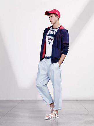 Cómo combinar: chubasquero azul marino, camiseta con cuello circular estampada en blanco y azul marino, pantalón chino celeste, sandalias de cuero blancas