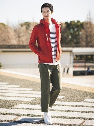 Cómo combinar: chubasquero rojo, camiseta de manga larga de rayas horizontales en blanco y azul marino, pantalón chino verde oliva, tenis blancos