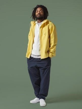 Cómo combinar un chubasquero amarillo: Ponte un chubasquero amarillo y un pantalón chino azul marino para un look diario sin parecer demasiado arreglada. Tenis de lona blancos son una opción muy buena para complementar tu atuendo.