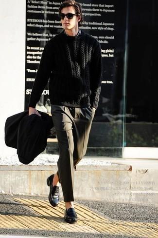Cómo combinar un jersey de ochos negro: Intenta ponerse un jersey de ochos negro y un pantalón de vestir verde oliva para rebosar clase y sofisticación. Este atuendo se complementa perfectamente con mocasín de cuero negro.