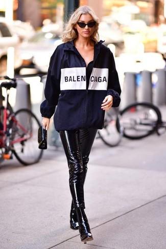 Cómo combinar: chubasquero estampado azul marino, pantalones pitillo de cuero negros, botines de cuero negros, cartera sobre de cuero negra
