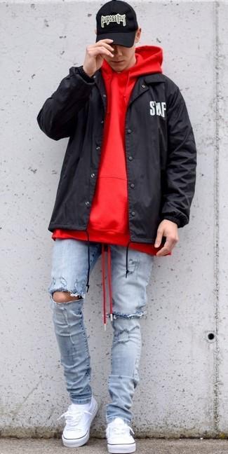 Cómo combinar: chubasquero negro, sudadera con capucha roja, vaqueros pitillo desgastados celestes, tenis de lona blancos