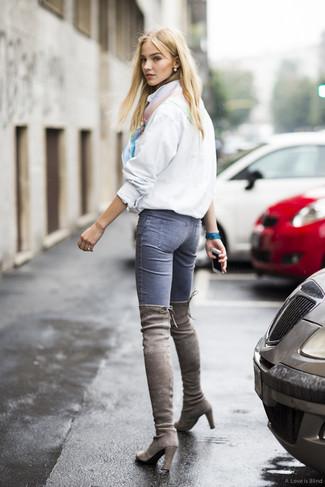 Cómo combinar: chubasquero blanco, vaqueros pitillo azules, botas sobre la rodilla de ante grises, bufanda de seda en multicolor