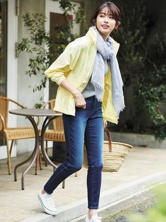 Cómo combinar: chubasquero amarillo, vaqueros pitillo azul marino, tenis de lona blancos, bolsa tote de paja marrón claro