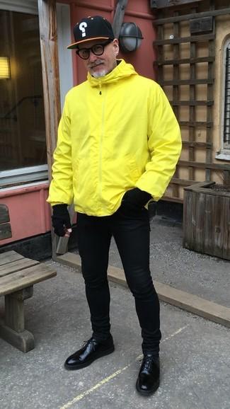 Cómo combinar: chubasquero amarillo, vaqueros pitillo negros, zapatos derby de cuero negros, gorra de béisbol estampada negra