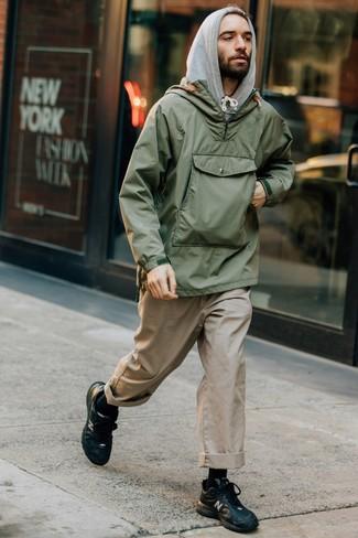 Cómo combinar: chubasquero verde oliva, sudadera con capucha gris, pantalón chino en beige, deportivas de cuero negras