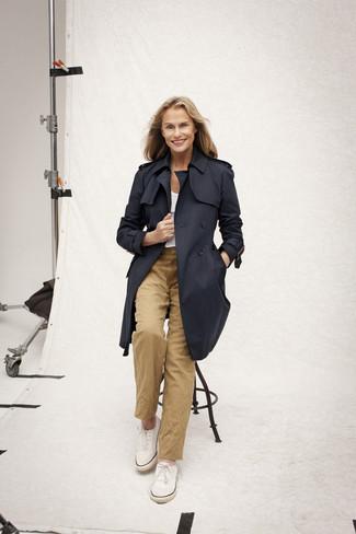 Look de Lauren Hutton: Gabardina Azul Marino, Camiseta con Cuello Circular Blanca, Pantalón Chino Marrón Claro, Zapatillas Plimsoll Blancas