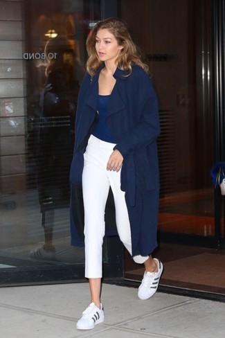 Cómo combinar: gabardina azul marino, camiseta sin manga azul marino, pantalones pitillo blancos, tenis de cuero en blanco y negro