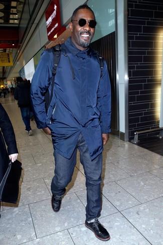 Look de Idris Elba: Gabardina Azul Marino, Vaqueros Azul Marino, Botas Safari de Cuero Negras, Mochila Azul Marino