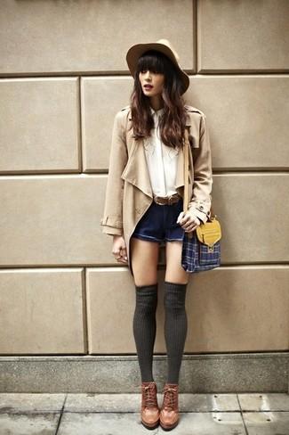 Cómo combinar: gabardina marrón claro, blusa de botones de seda blanca, pantalones cortos vaqueros azul marino, botines con cordones de cuero marrónes