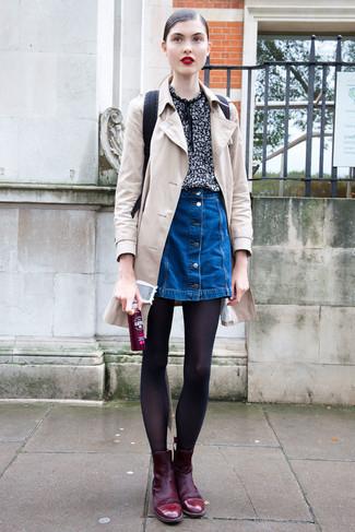 Cómo combinar: gabardina en beige, blusa de manga corta estampada negra, falda con botones vaquera azul, botines de ante burdeos