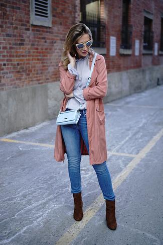 Cómo combinar: gabardina ligera rosada, blusa de manga larga violeta claro, vaqueros pitillo azules, botines de ante en marrón oscuro