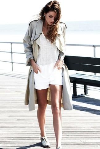 Cómo combinar: gabardina en beige, blusa sin mangas de crochet blanca, pantalones cortos blancos, zapatos oxford de cuero en blanco y negro