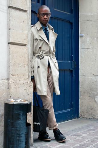 Cómo combinar: gabardina en beige, camisa de manga larga de cambray azul, pantalón chino marrón claro, botas safari de cuero negras