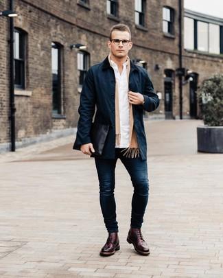 Cómo combinar: gabardina azul marino, camisa de manga larga blanca, vaqueros pitillo azul marino, zapatos brogue de cuero burdeos