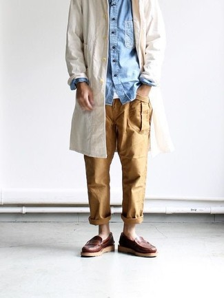 Cómo combinar: gabardina en beige, camisa vaquera celeste, camiseta con cuello circular blanca, pantalón chino marrón claro
