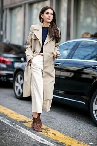 Cómo combinar: gabardina en beige, camiseta con cuello circular negra, falda pantalón blanca, botas planas con cordones de cuero marrónes