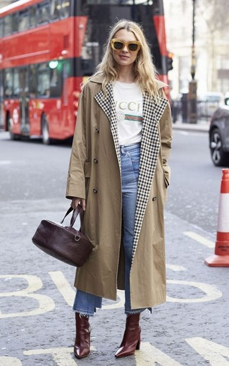 Cómo combinar: gabardina marrón claro, camiseta con cuello circular estampada blanca, falda pantalón vaquera celeste, botines de cuero burdeos